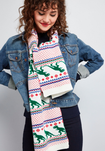 Model wears white, red, and green dinosaur-print scarf with a jean jacket and black skirt