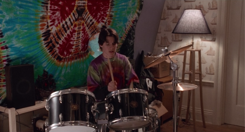 Max playing on the drums while wearing tie-dye.