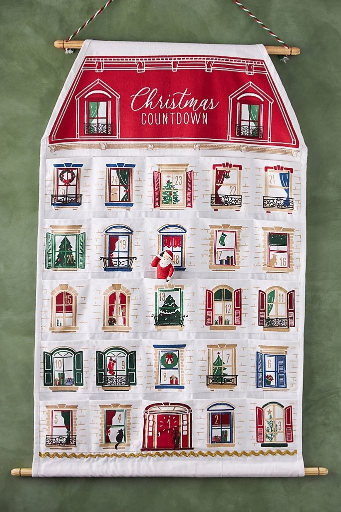 a hanging white house made of cloth with windows filled with holiday decor that are actually pockets