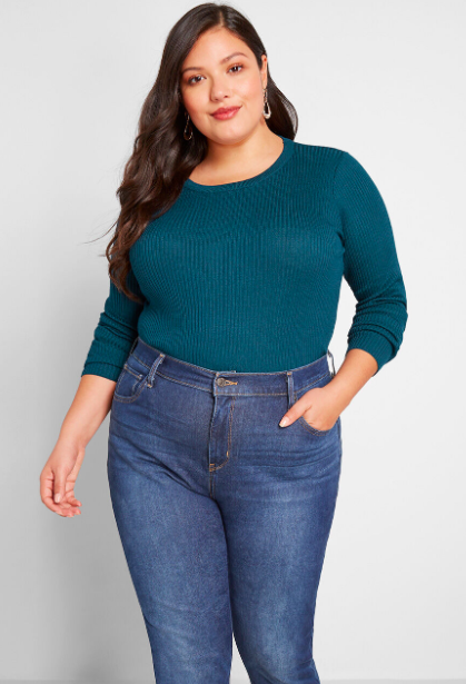 Model wears teal ribbed pullover sweater with blue jeans