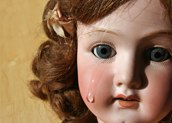A porcelain doll has a tear running down its chest