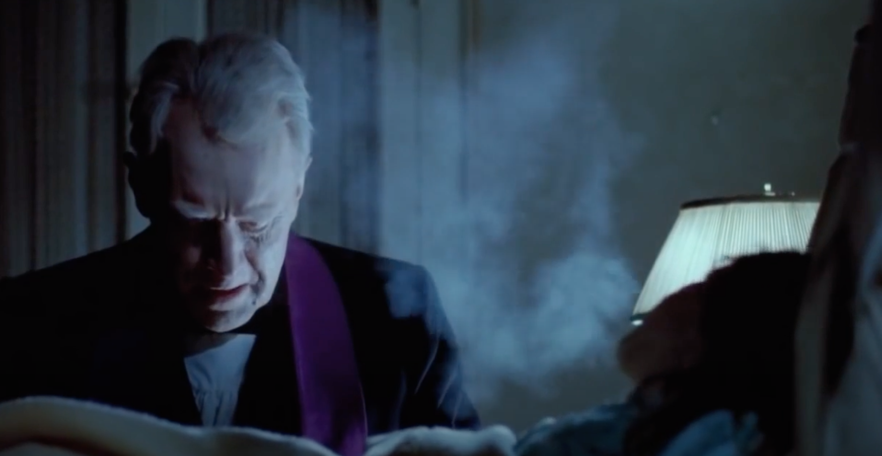 A priest sits next to young girl while performing an exorcism.