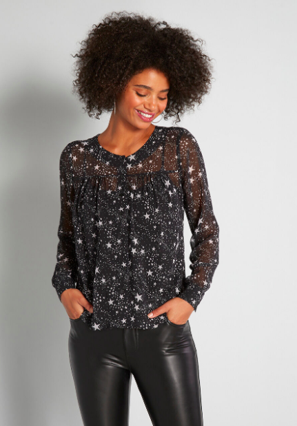 Model wears long sleeve starry sheer blouse with leather leggings
