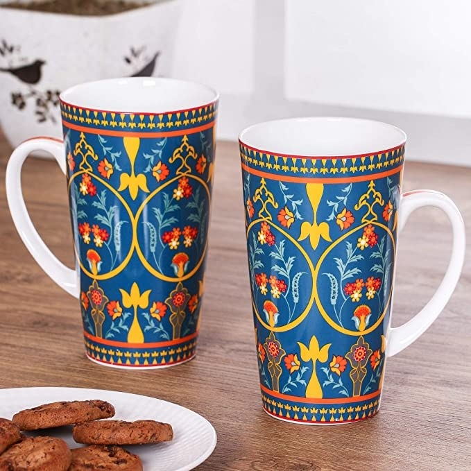 Two mugs on a wooden table with a plate of biscuits near them.