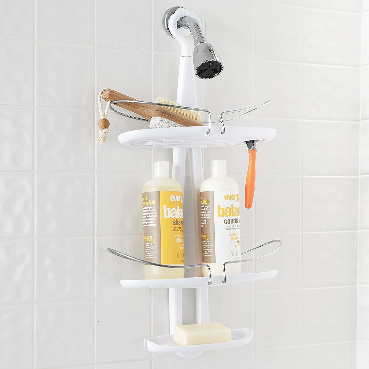 The shower caddy hanging onto a showerhead, pictured with bath products.