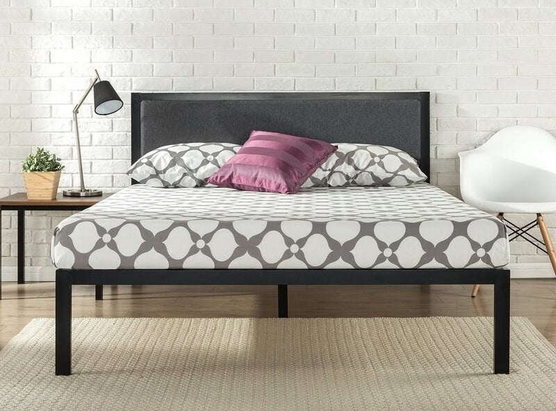 A black bed frame with gray upholstered headboard filled with foam