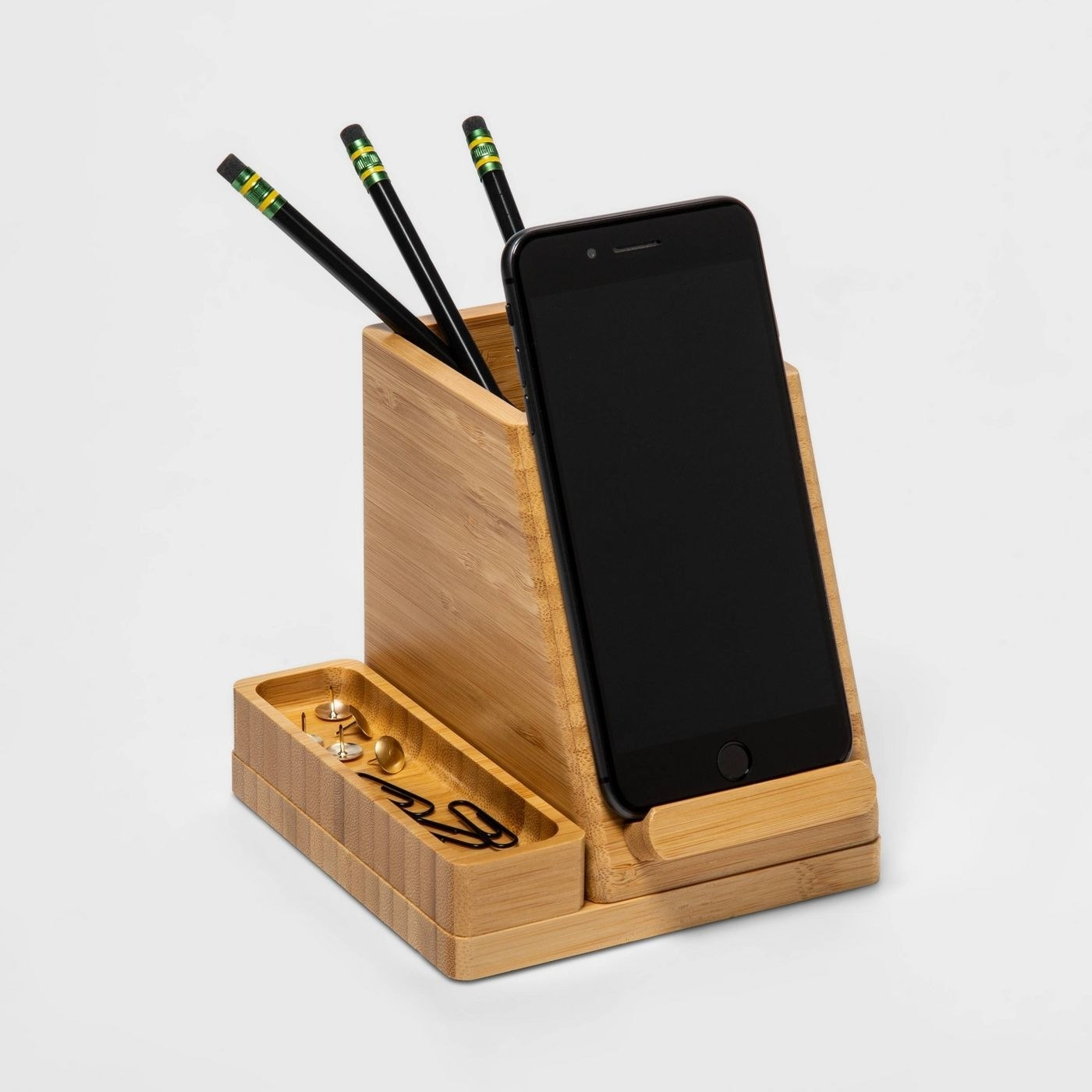 The desk organizer, which is comprised of a rectangular pencil up with an angled phone stand in front of it, and a small oblong container for paper clips or rubber bands on the left side