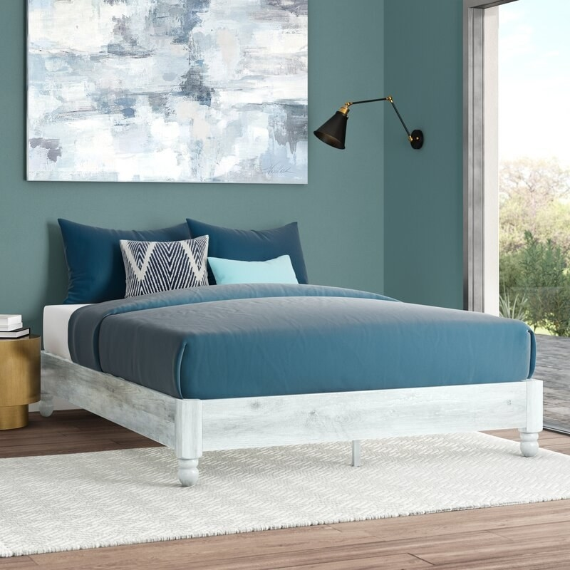 A white wooden bed frame without headboard