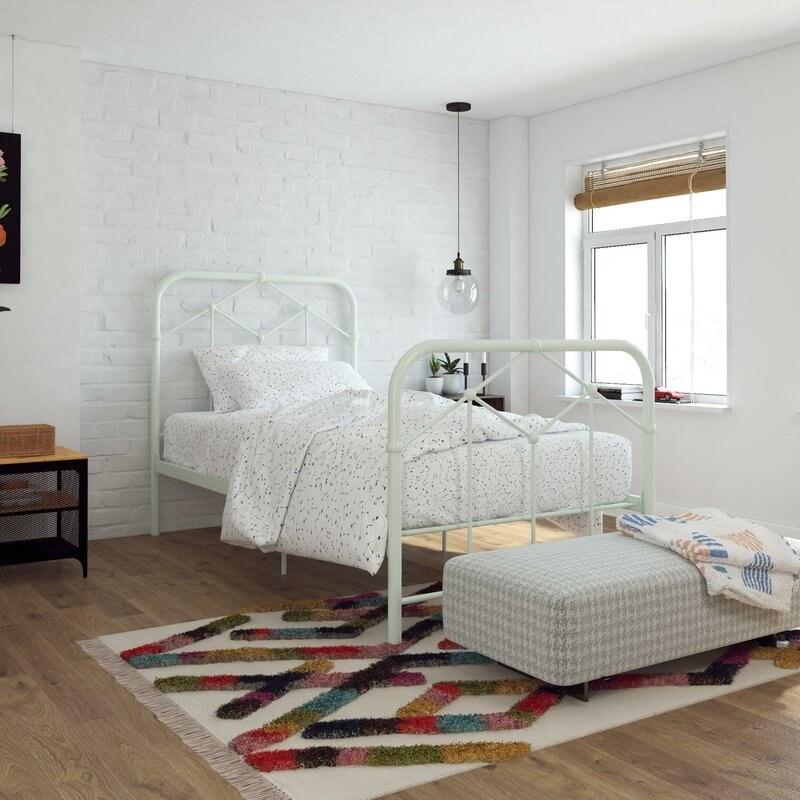 A light green metal farmhouse bed frame