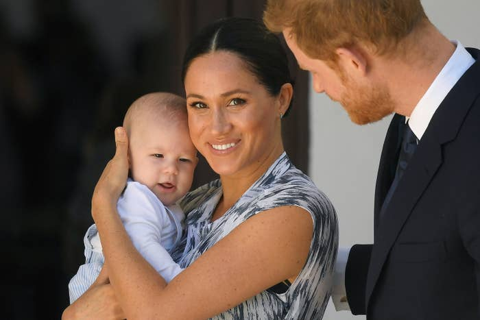 Meghan Markle holding baby Archie while Prince Harry watches