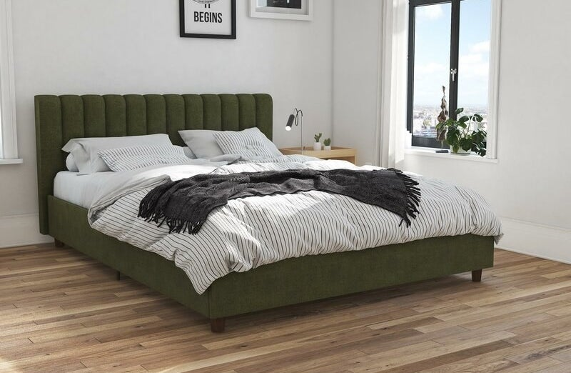 A green upholstered bed frame with vertical tufted headboard