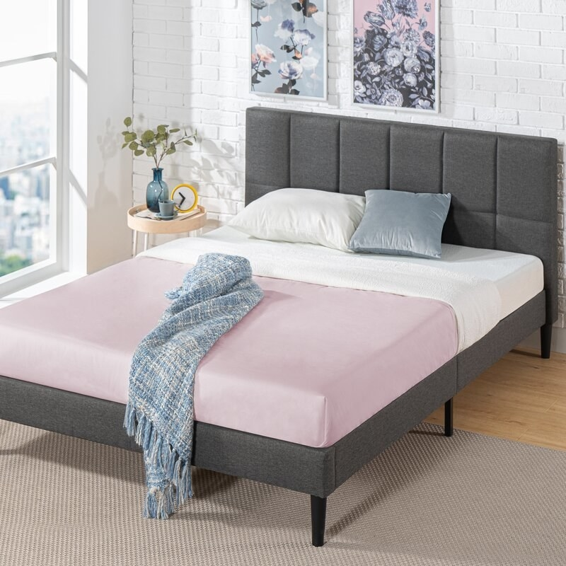 A dark gray bed frame with upholstered headboard