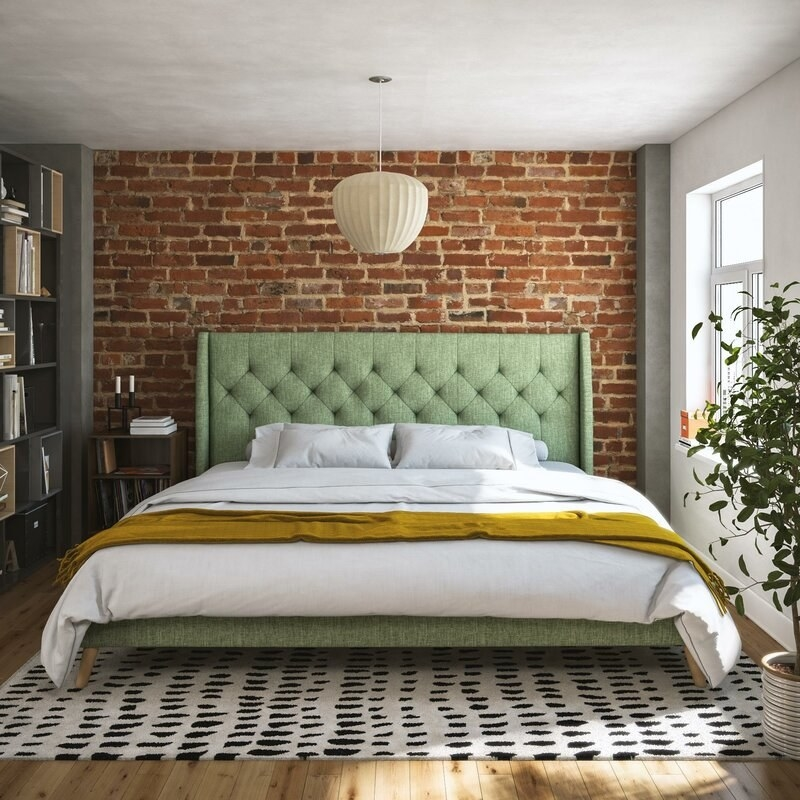 A sage green upholstered bed frame with tufted headboard