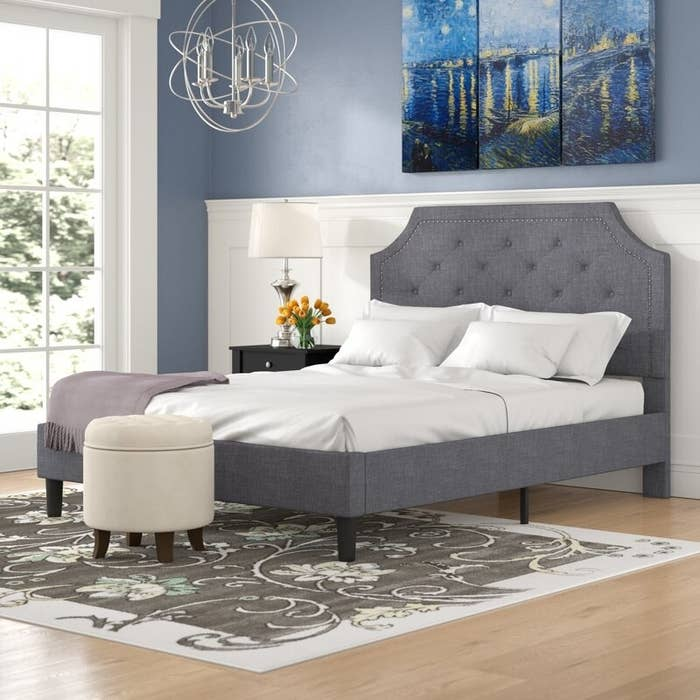 Gray bed frame with upholstered tufted headboard and nailhead trim