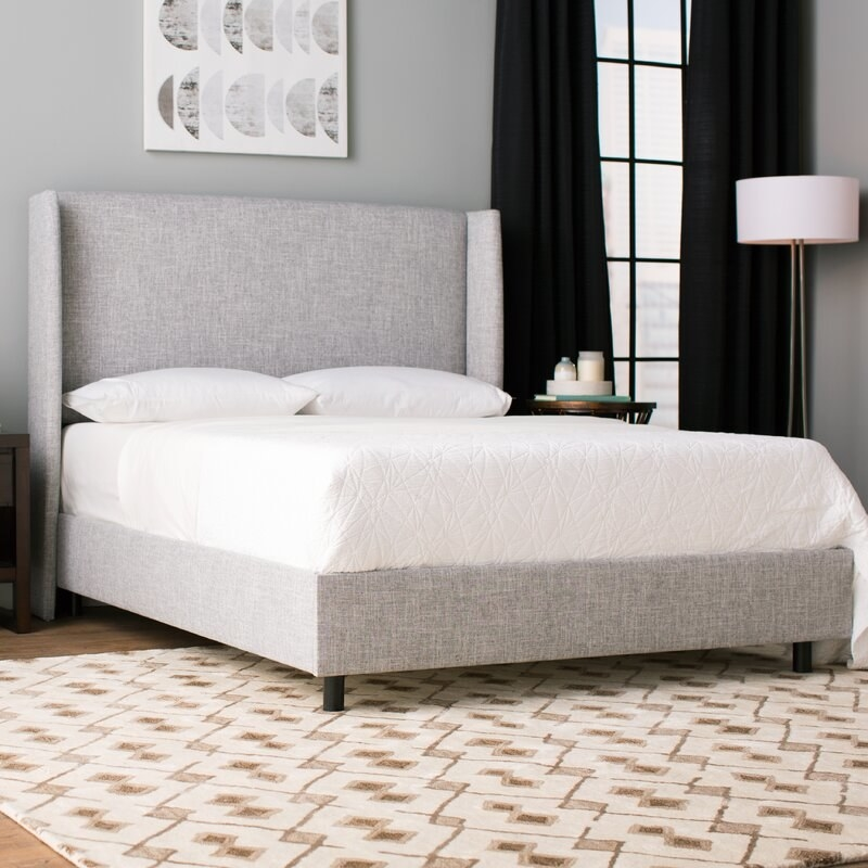 A gray upholstered bed frame with large headboard