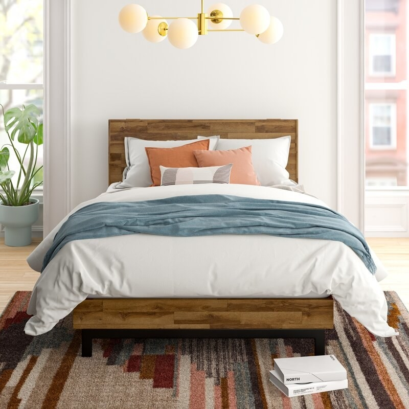 A wooden bed frame with headboard and metal legs