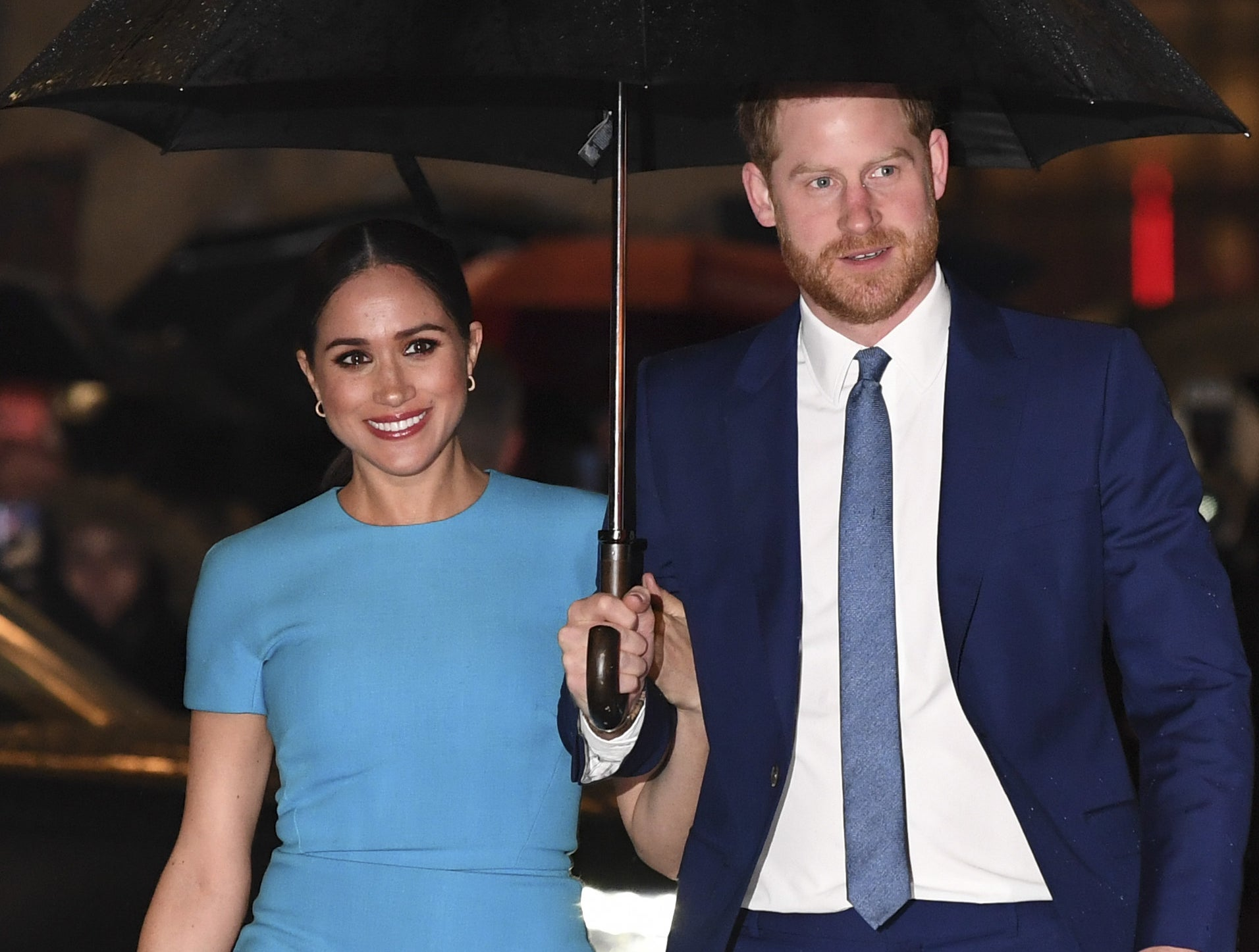 Meghan Markle and Prince Harry walking underneath an umbrella