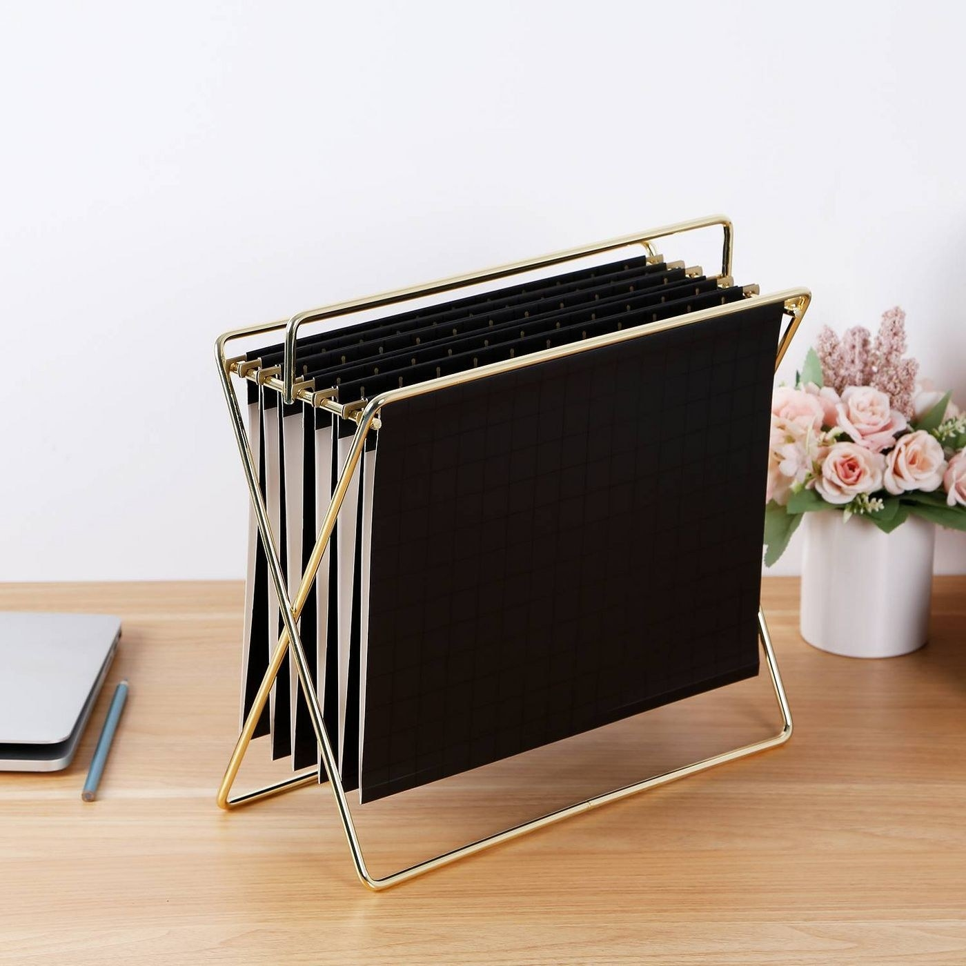 The gold-colored file hanger, which is collapsable and comprised of two frame pieces and bars between them that hang the files
