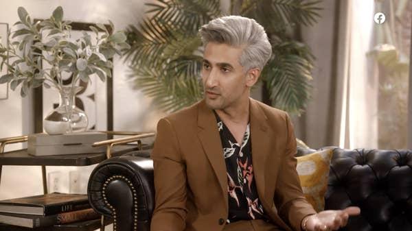 Tan berbicara di sofa dengan setelan jas