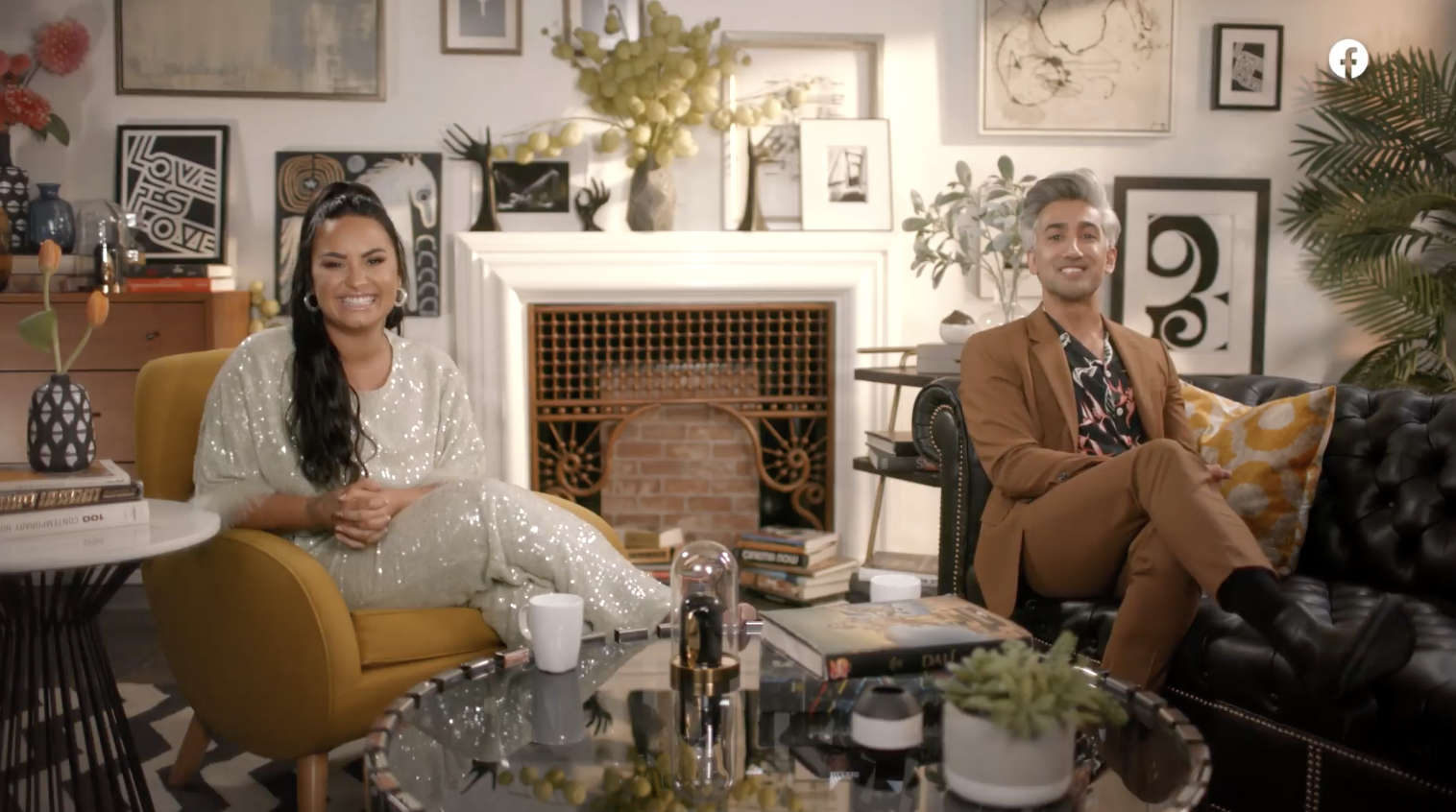 Demi and Tan smiling on couches