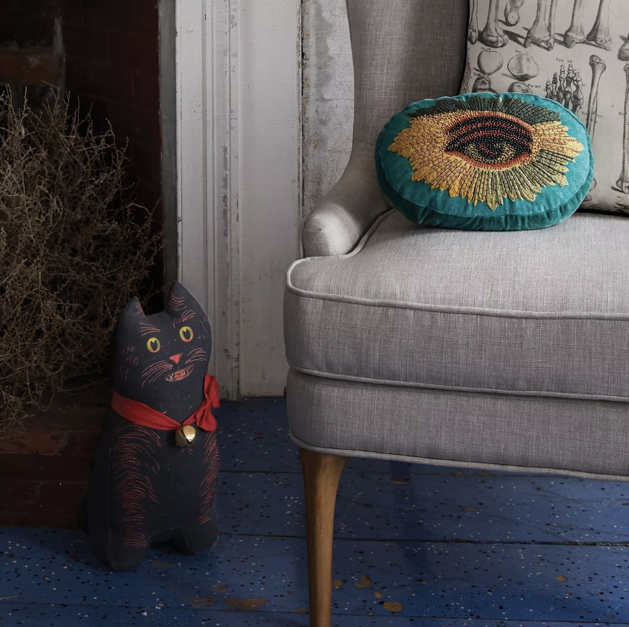 Beady-eyed embellished throw pillow on an armchair
