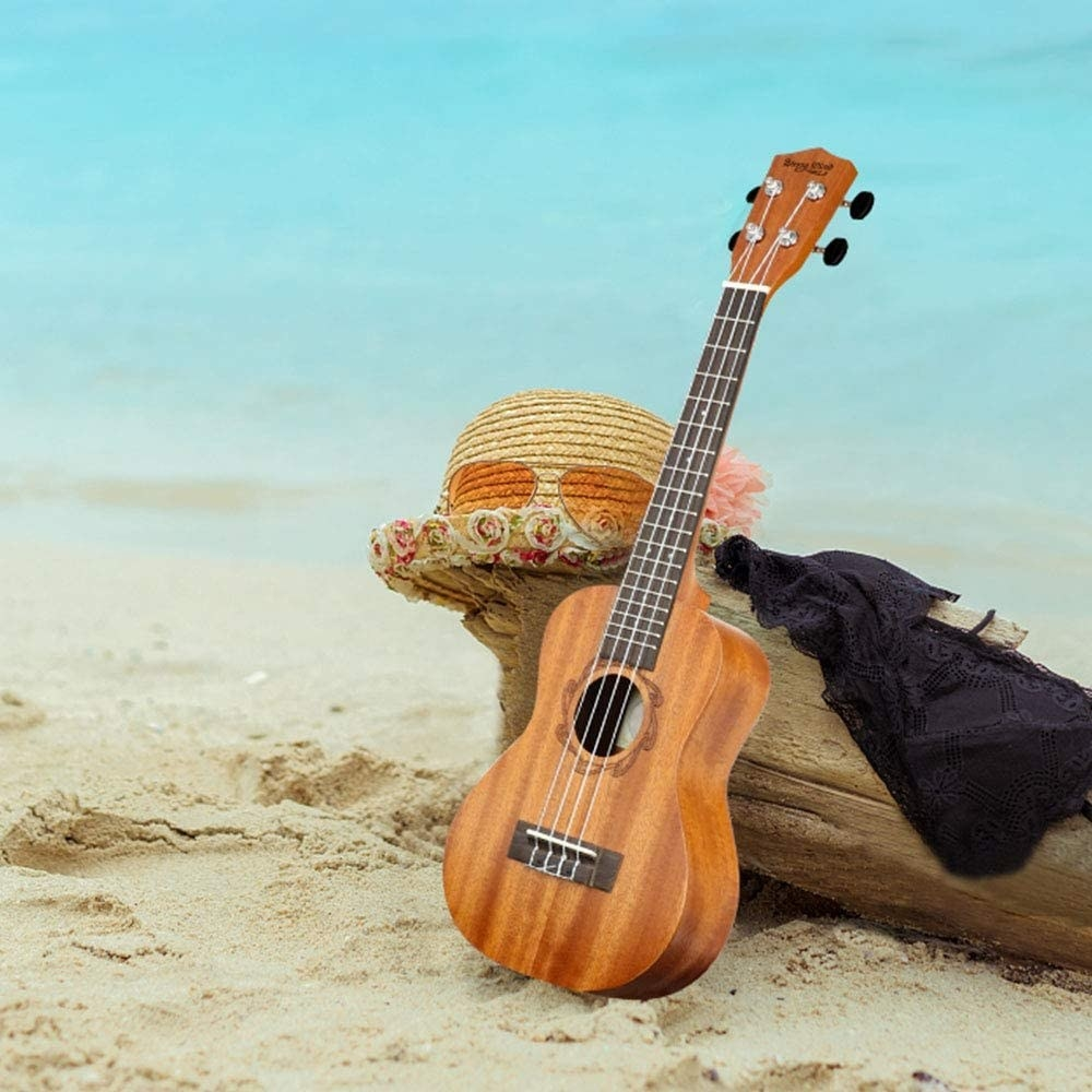 A ukulele leaning against a log on the beach