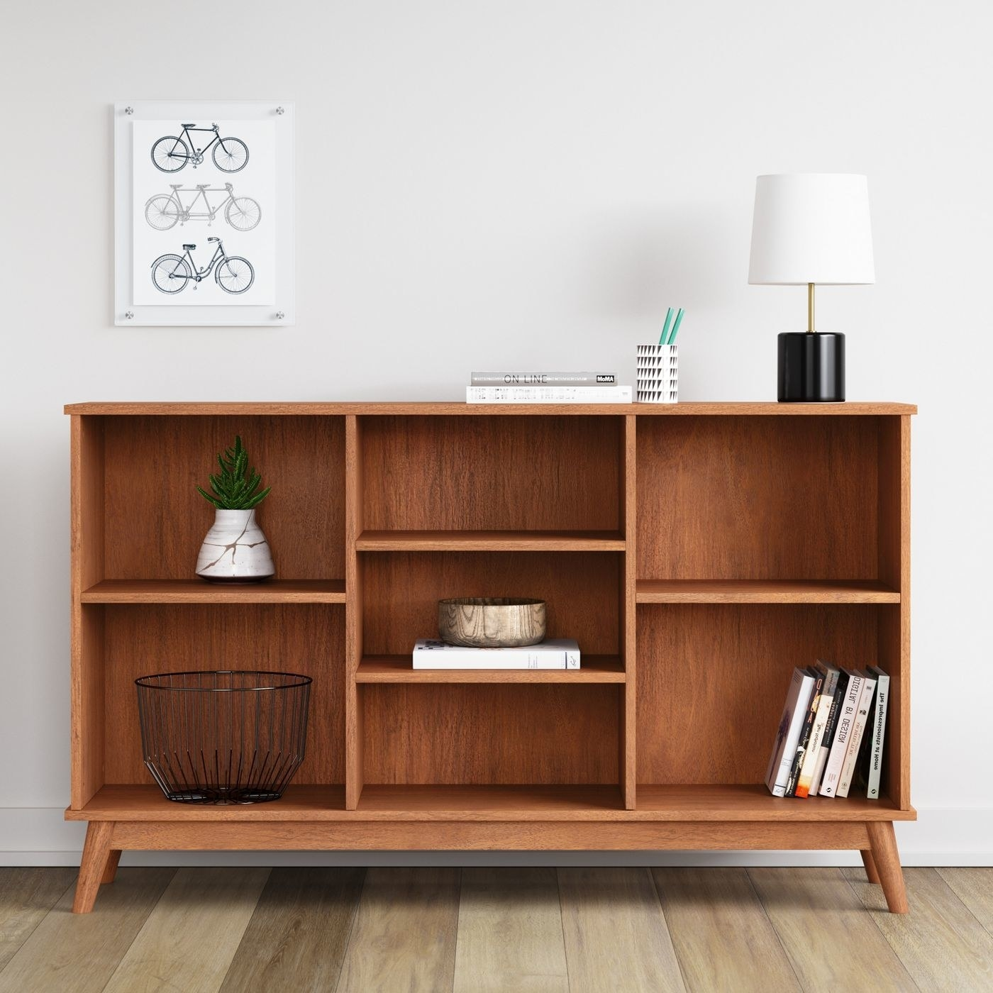 Low-rise horizontal bookshelf, with two shelves large enough for books or large decorative objects on either side, and three smaller shelves in the middle of the case