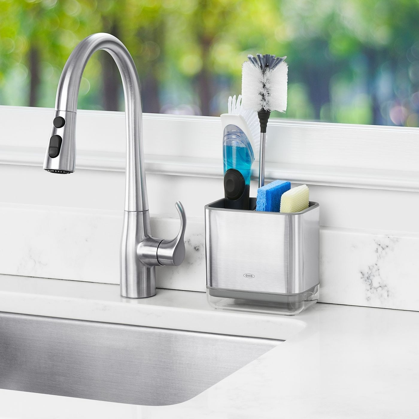 The caddy, which is rectangular and brushed stainless steel, slightly elevated with a small drip tray