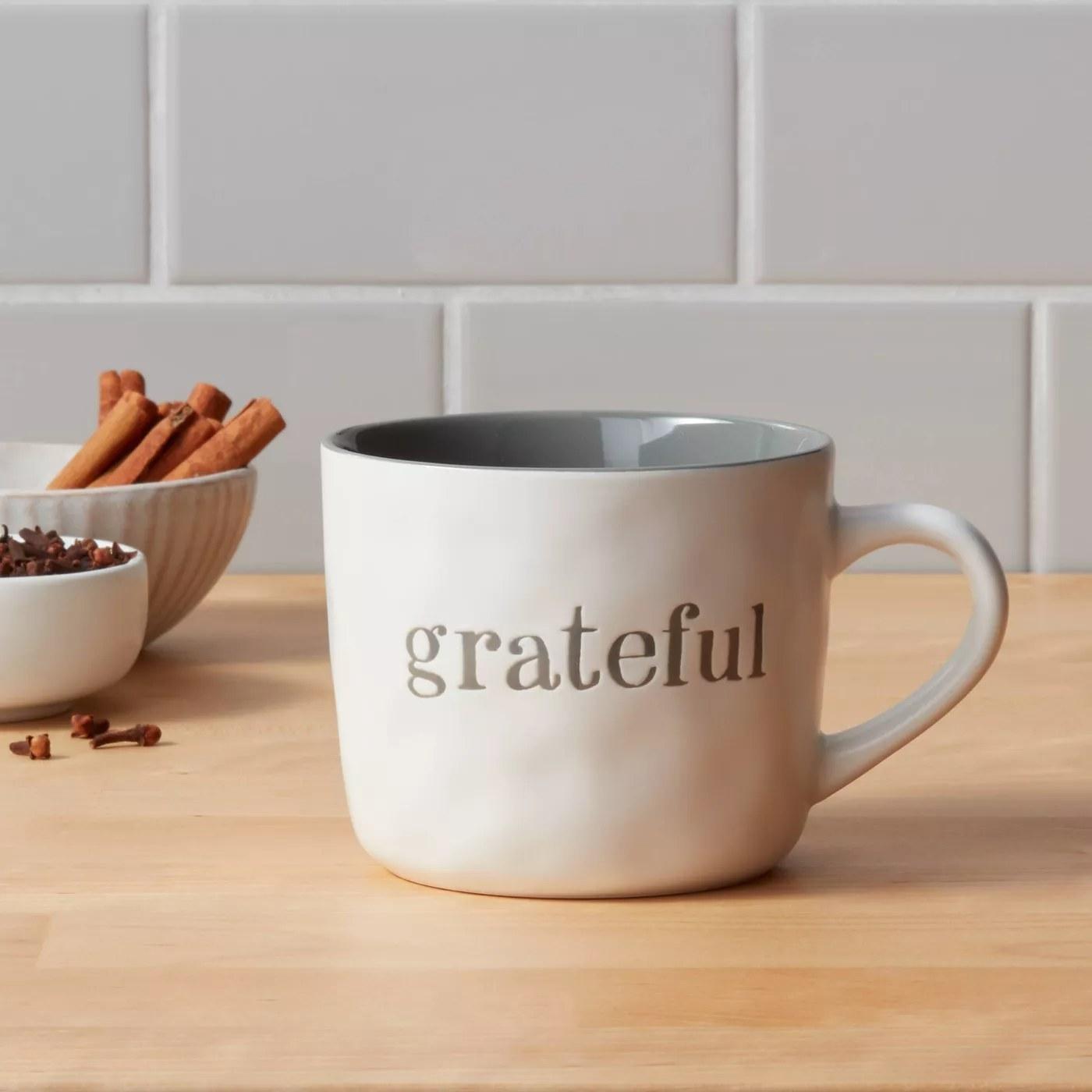 "The mug that says ""grateful"" on it"