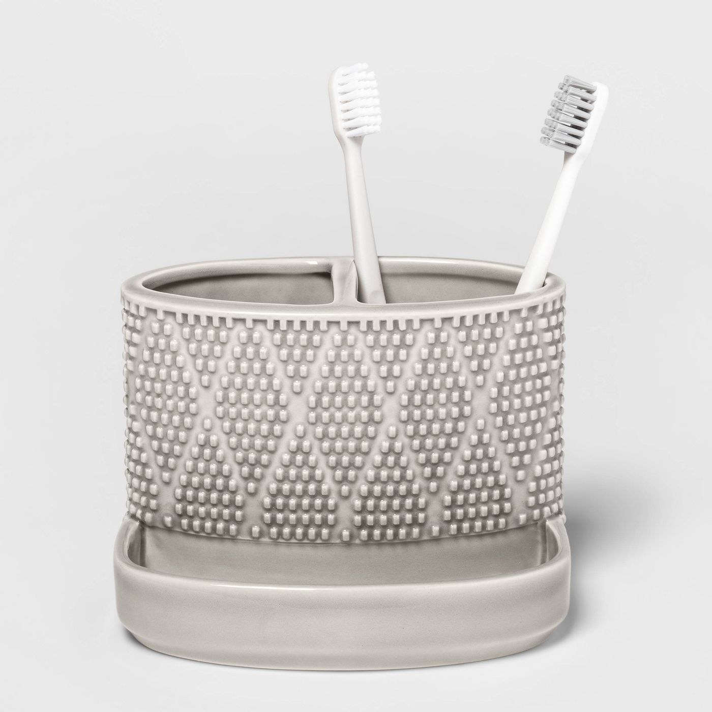 The grey caddy, which is cup-shaped, with a divided running across the middle of the cup, and a small tray extending from the base for floss, etc