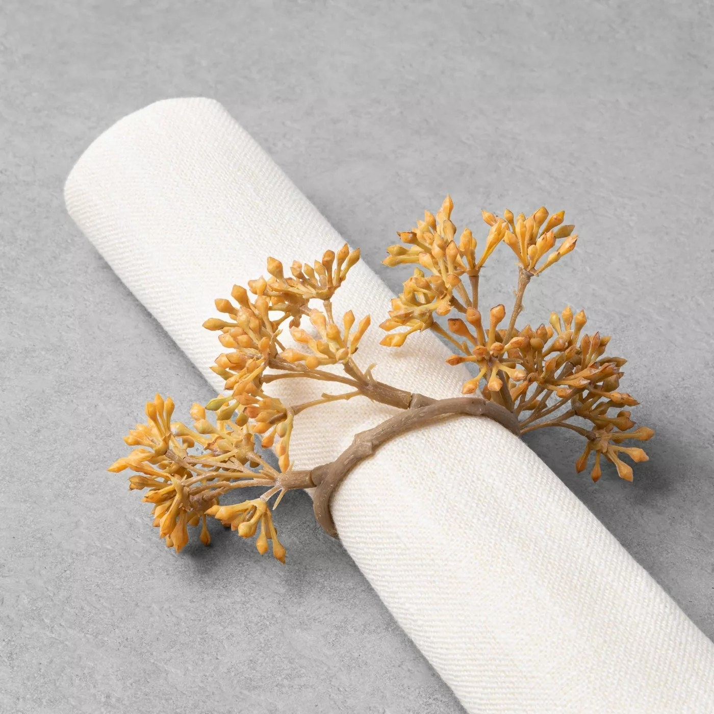 The napkin ring with faux flowers holding a napkin together