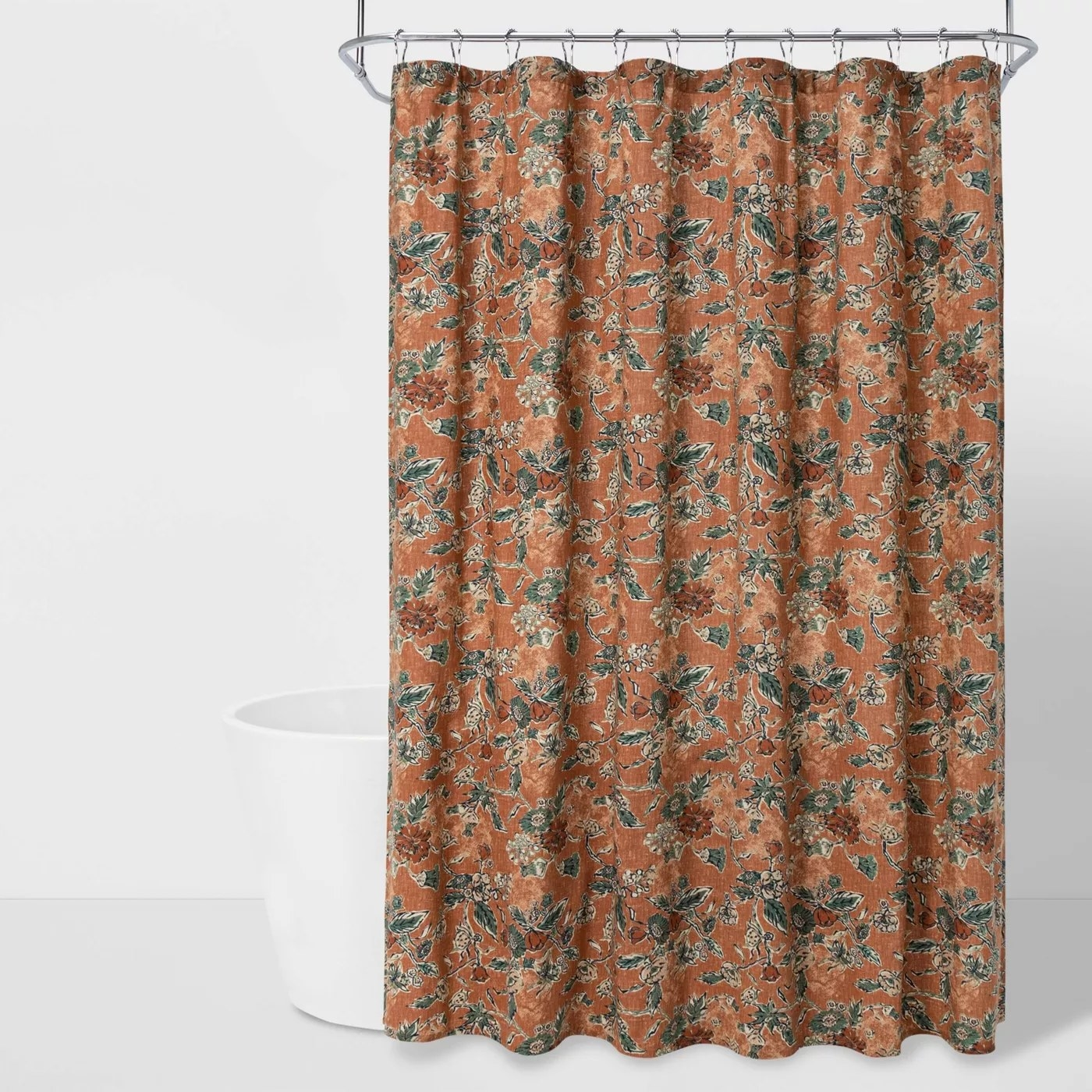 The orange and green floral shower curtain in a bathroom