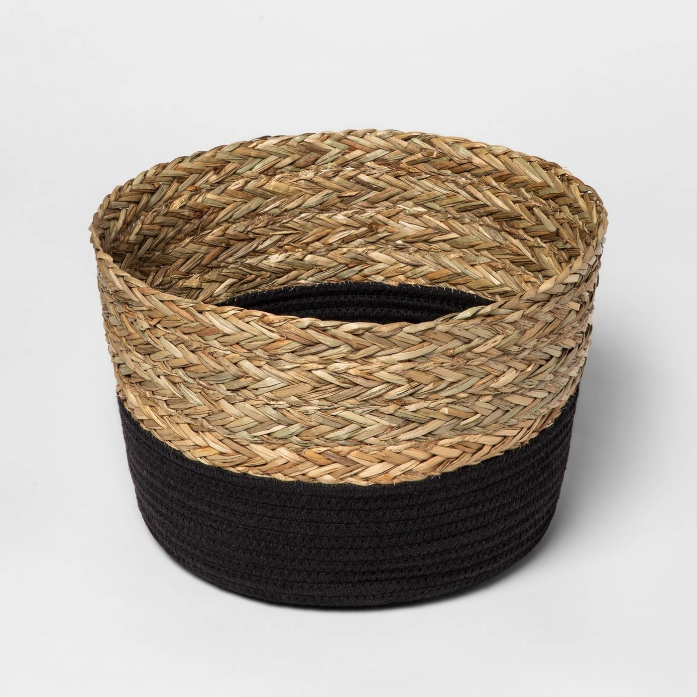 The rope basket, made from coiled black rope at the bottom, and braided straw-colored rope at the top, with a circular shape and open top