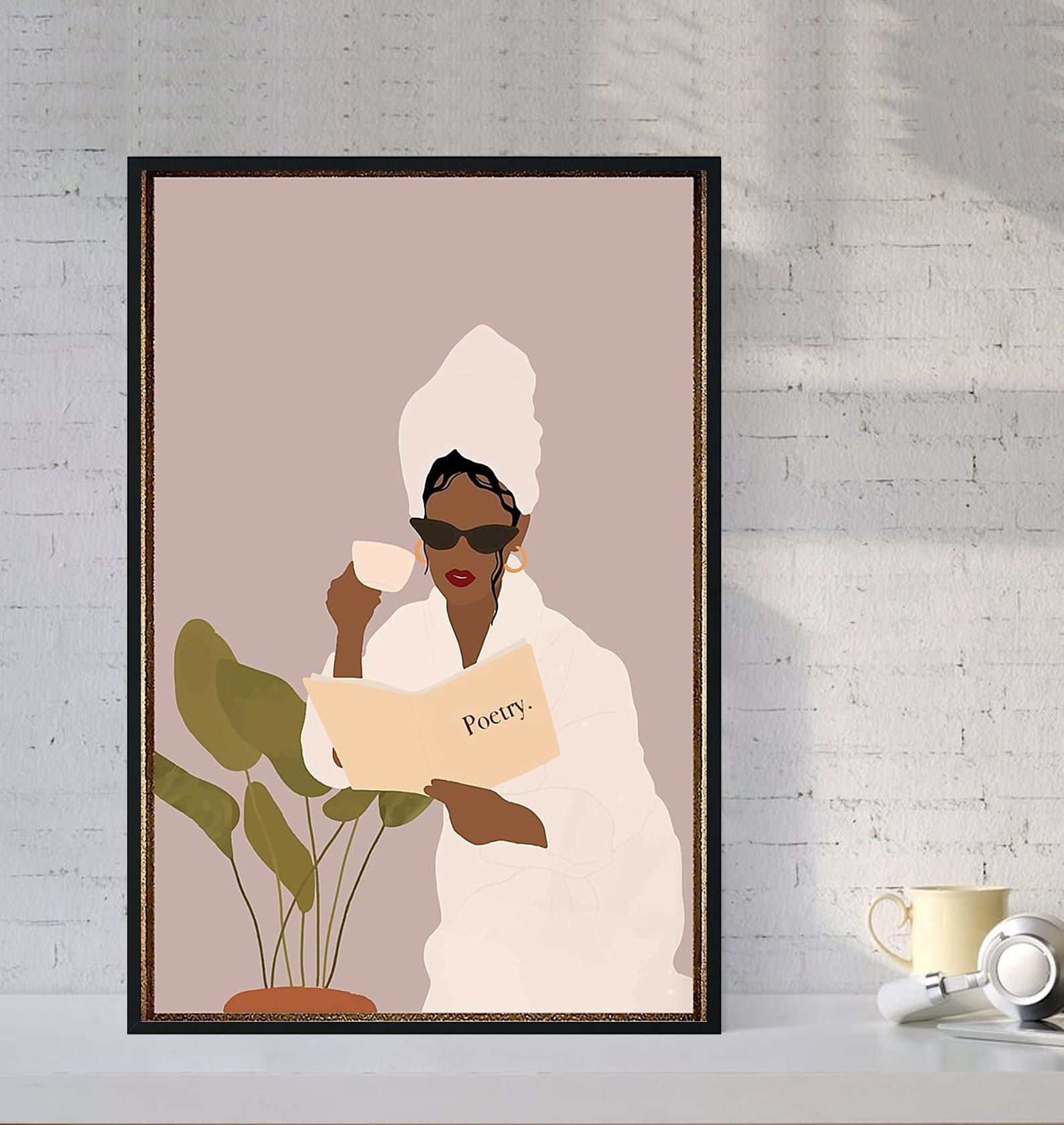 A print of a woman in red lipstick, sunglasses, a robe, and a hair towel drinking coffee and reading a book of poetry while sitting near a plant