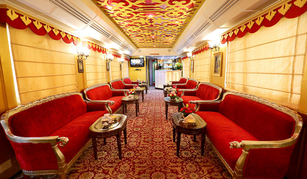 A luxurious train carriage with an ornate ceiling, plush red and gold couches, tables with flowers, glowing lamps, and a patterned carpet