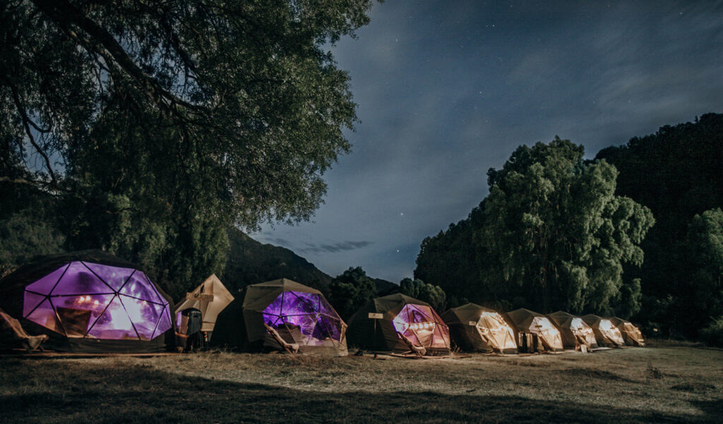 A row of geometric tents in a field at night