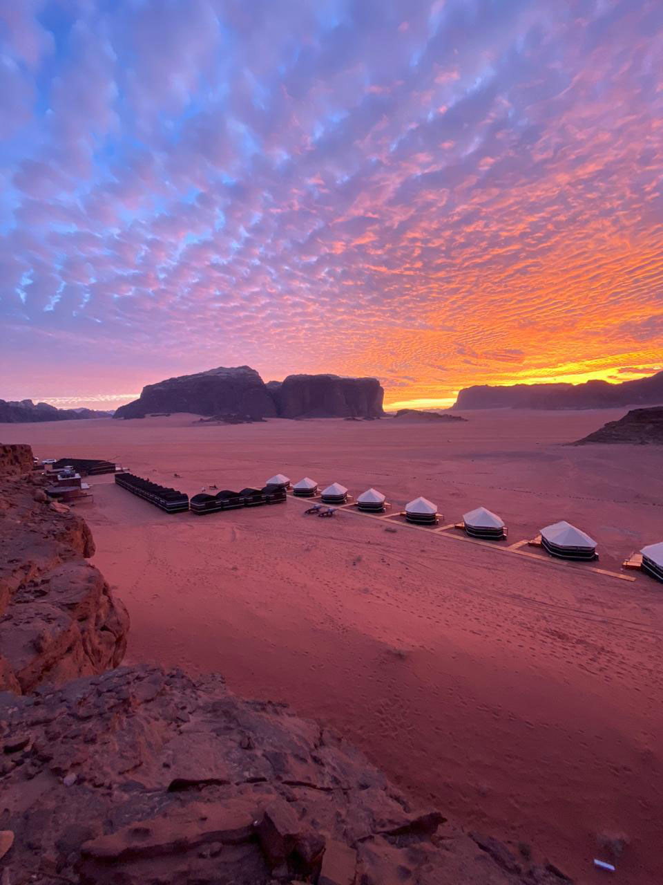 A purple and orange sunset over the desert where permanent tents are set up among sand dunes