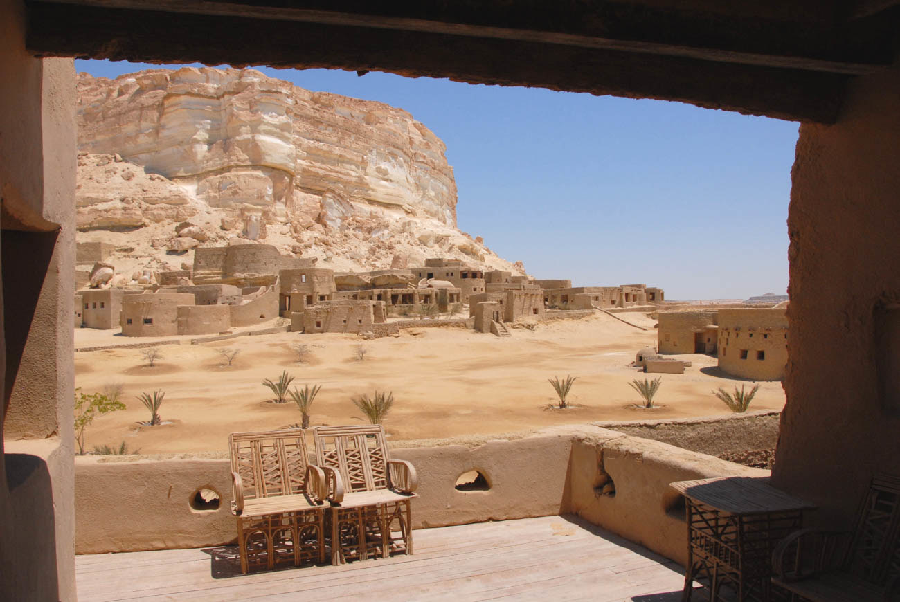 Looking out the window of a hotel room at the desert, the walls and furniture all blend in with the landscape