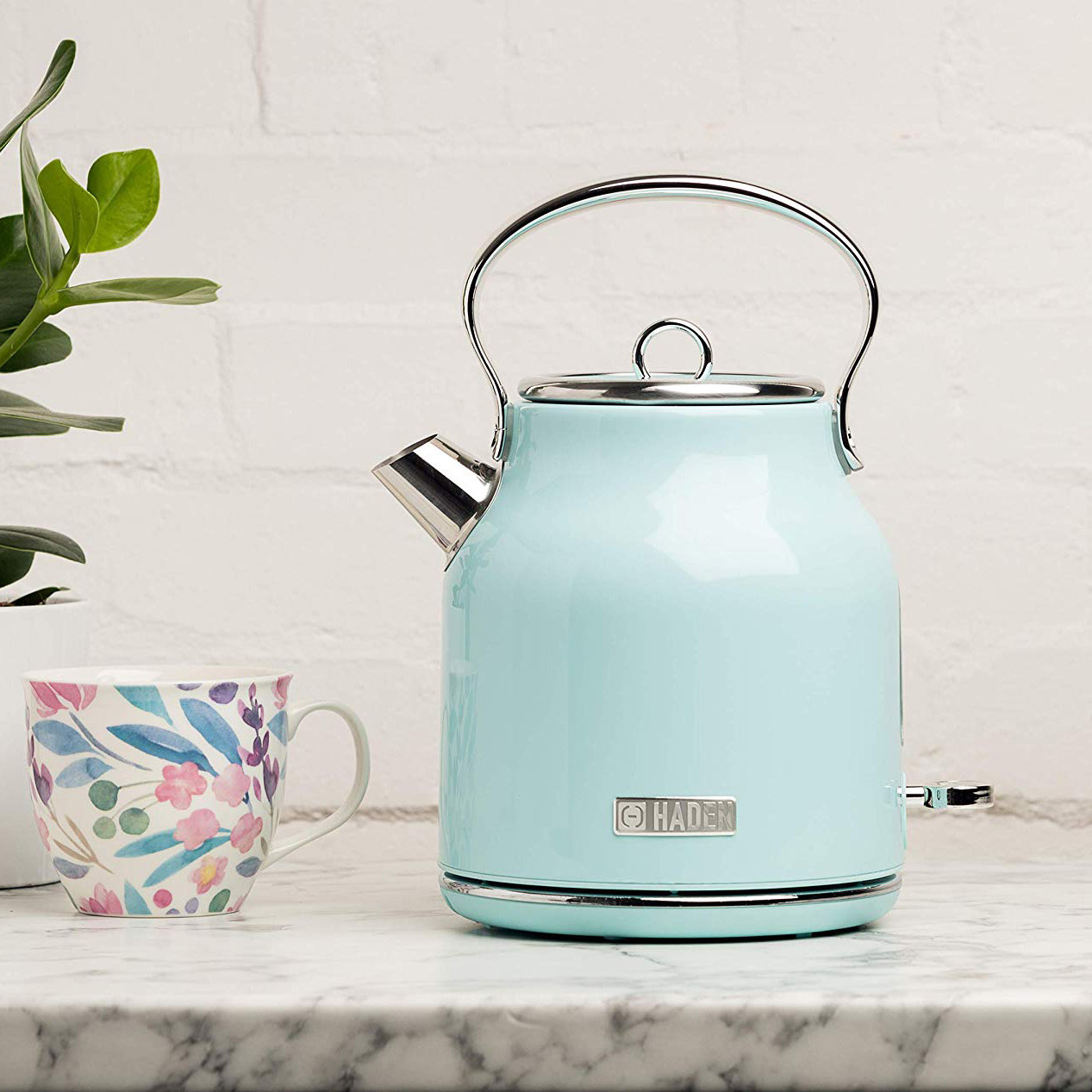 The tea kettle in light blue, with silver handle, lid and spout