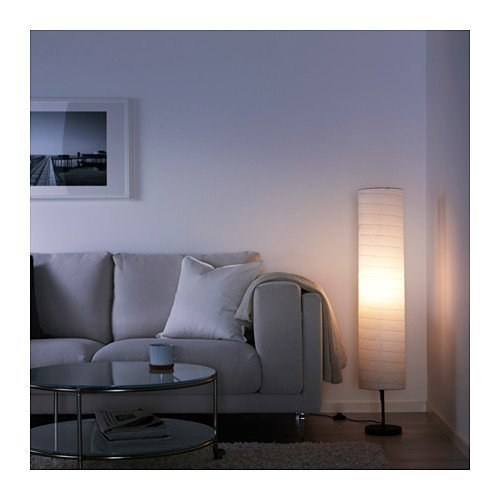 A cylindrical rice paper lamp kept in the corner of a room next to a grey sofa.