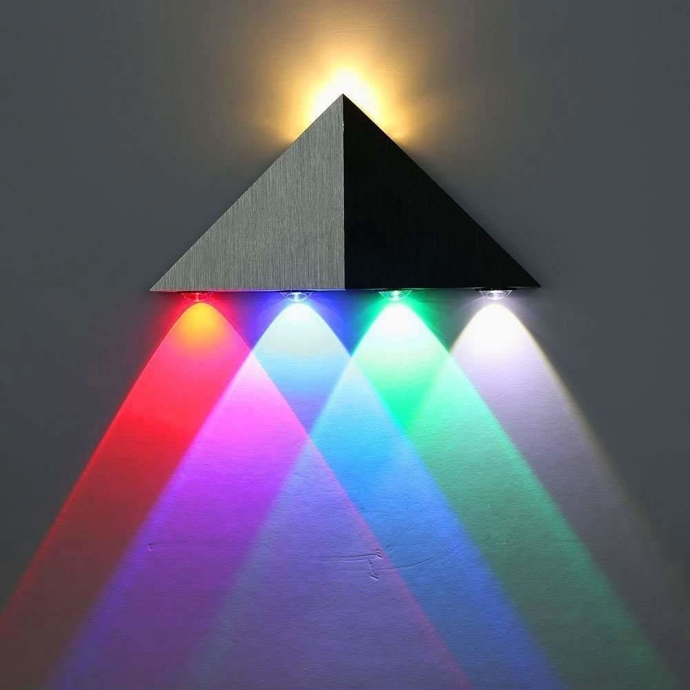 A triangular black wall sconce throwing out multi-coloured lights.
