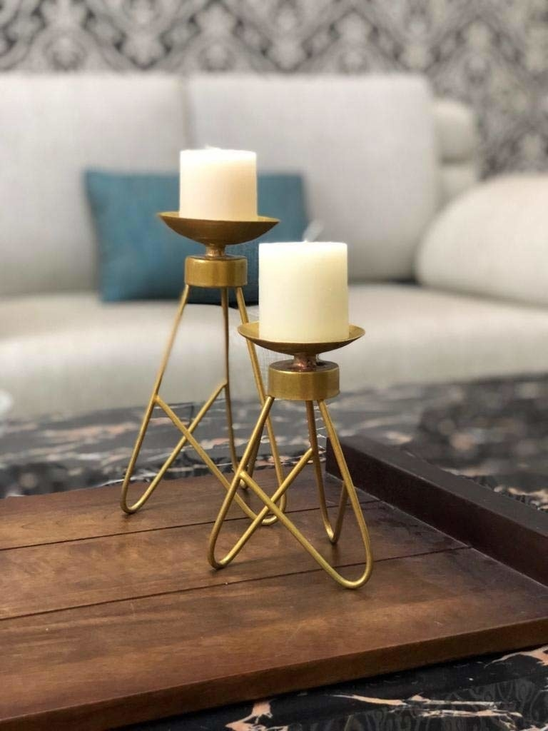 Two tripod candle holders with candles placed on them.