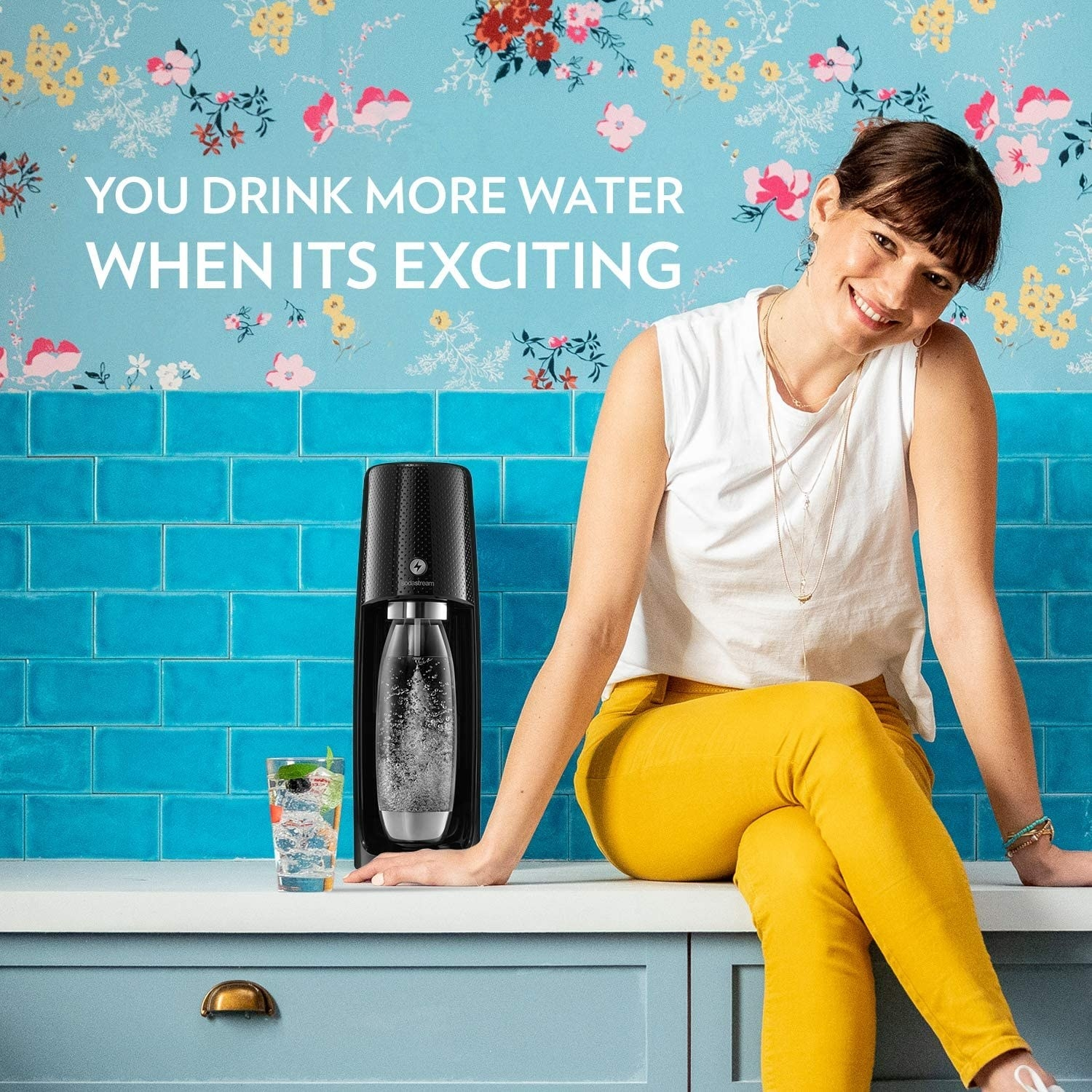 Model sits beside a glass of sparkling water and the black SodaStream sparkling water maker