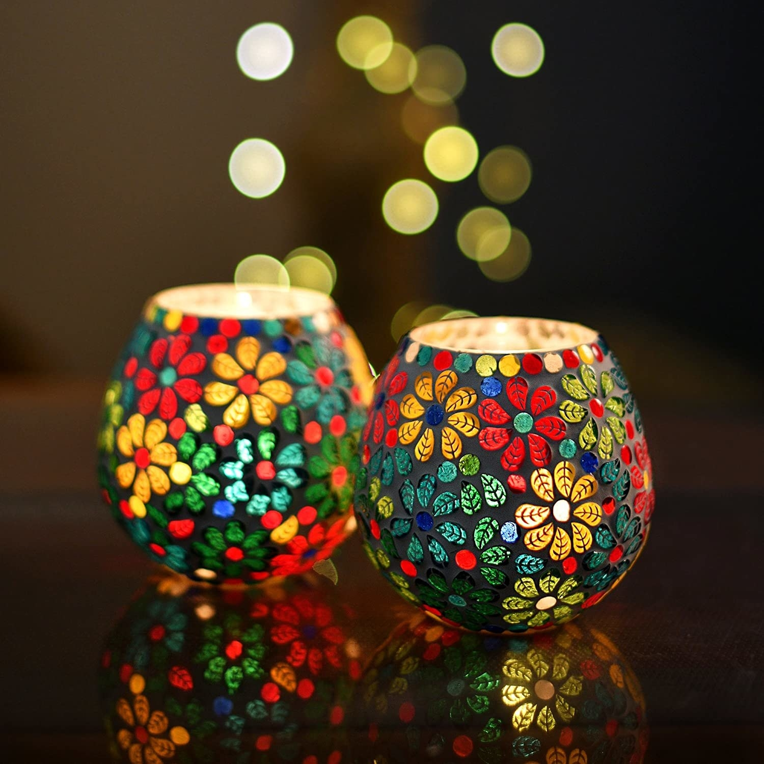 Two candles holders with a multi-coloured floral design.