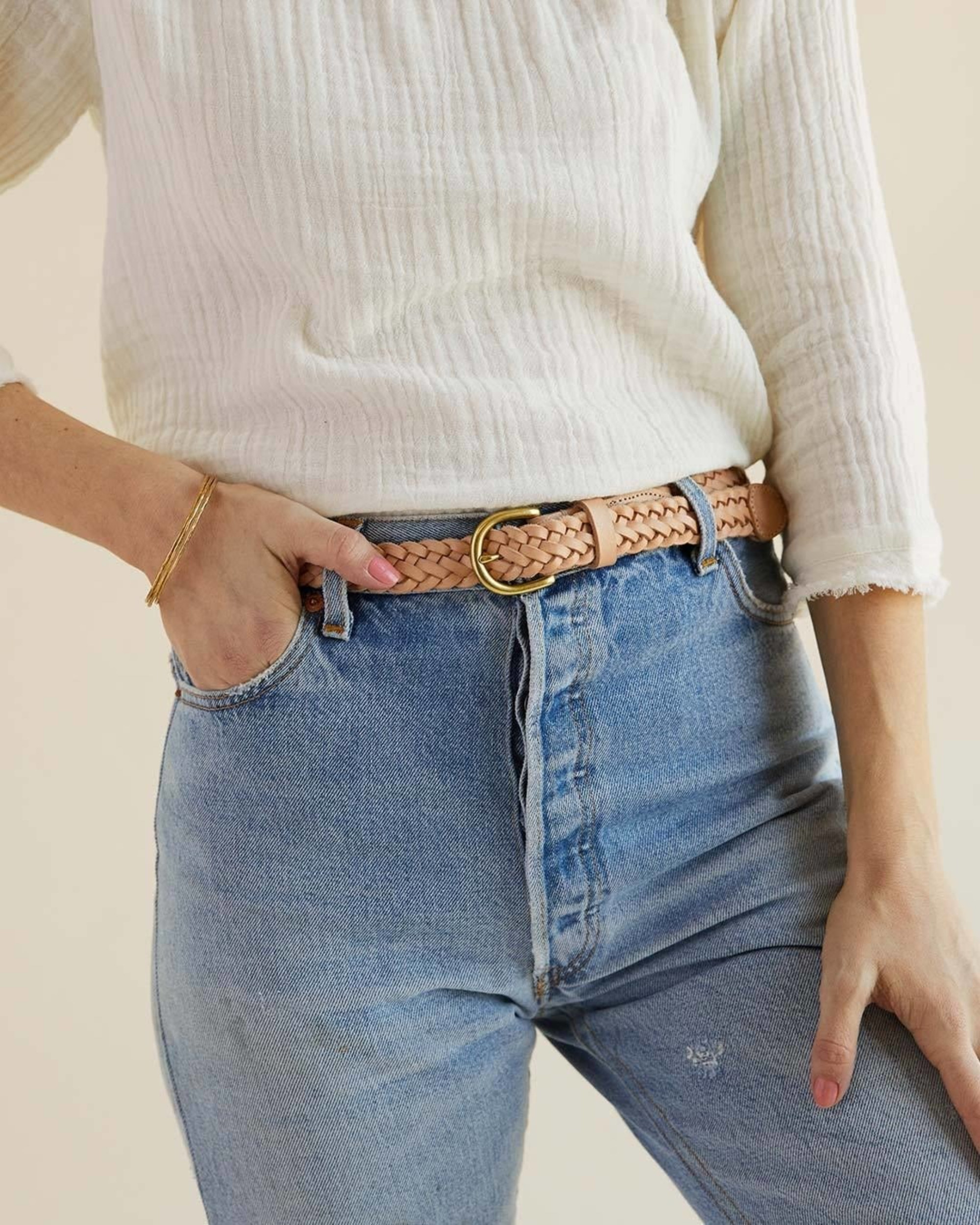 A model wearing the tan braided belt with a gold buckle with jeans