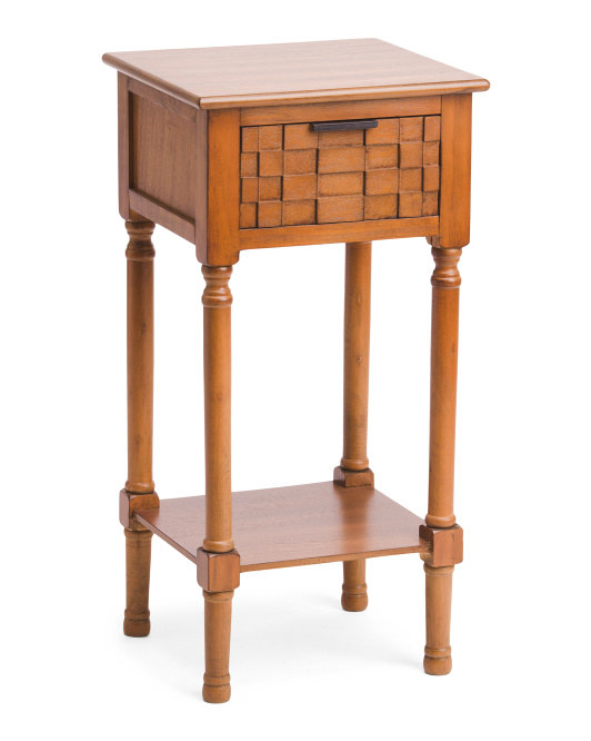 A tall square table with a shelf at the bottom and a pull-out drawer with a woven pattern