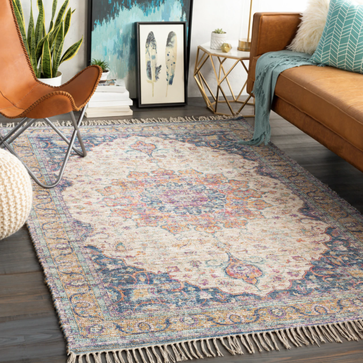 A rectangular rug with a khaki, saffron, violet, aqua, and white faded floral design and white tassels