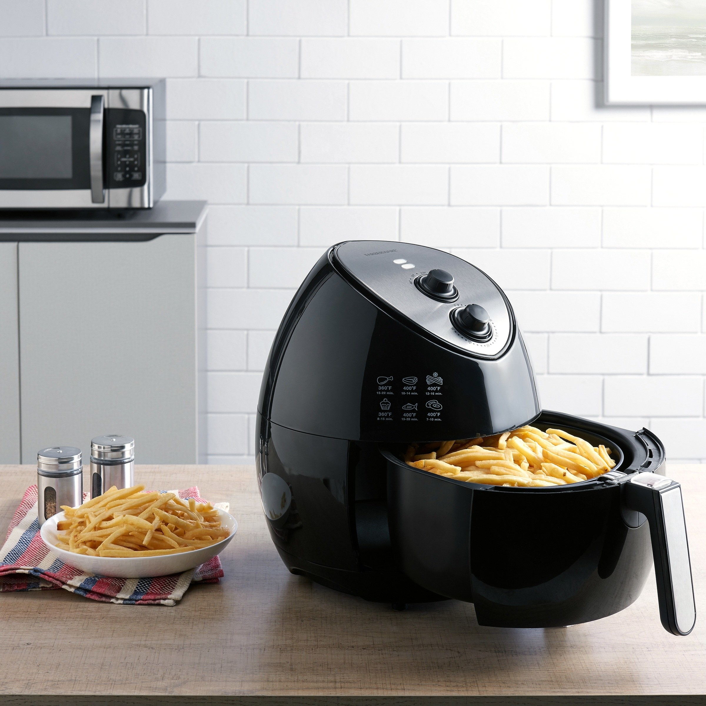 The small black air fryer, with its cooking basket open