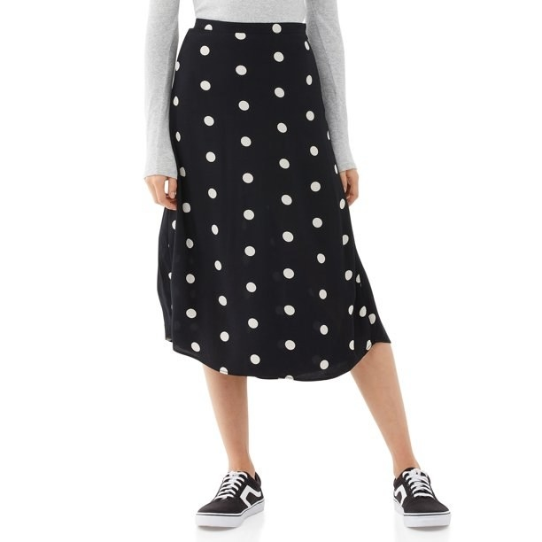 Model in black and white polka dot skirt and sneakers