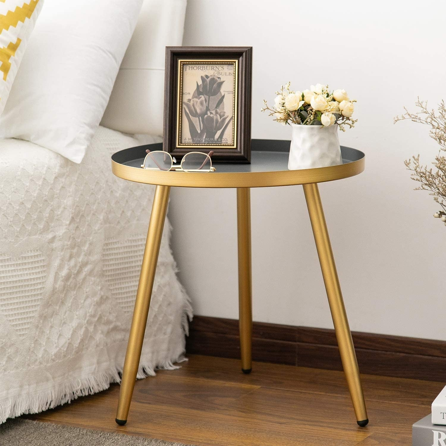 The circular table in a gold metallic tone holding a small flower pot, glasses, and a photo frame